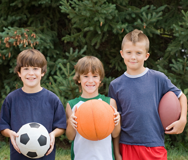 three young boys smiling and playing sports